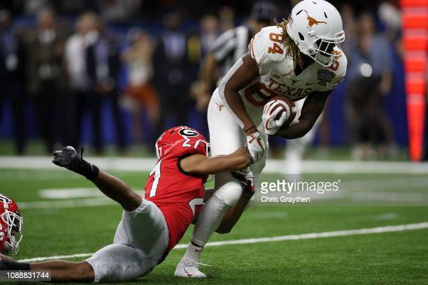 Lil'Jordan Humphrey of the Texas Longhorns runs for a first down as he is tackled by Eric Stokes of the Georgia Bulldogs at Mercedes-Benz Superdome...