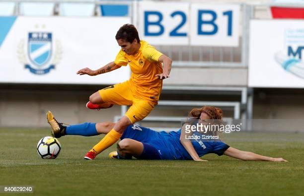 Lilla Turanyi of MTK Hungaria FC slide tackles Gulnara Gabelia of WFC BIIKKazygurt during the UEFA Women's Champions League Qualifying match between...