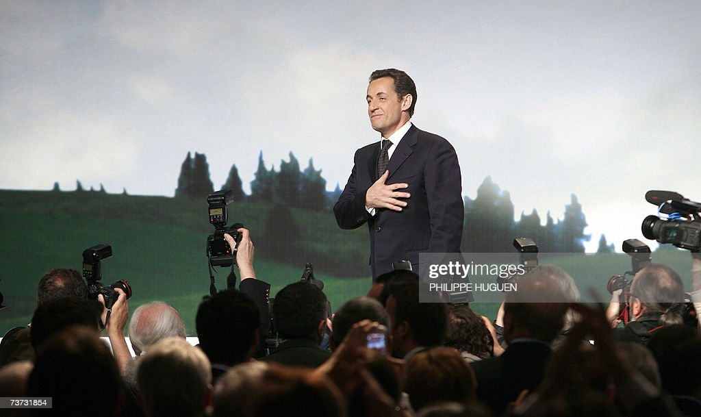 French right-wing presidential candidate Nicolas Sarkozy (C) arrives on the stage of the Zenith of Lille to hold a meeting as part of his political visit in the nothern France as part of his campaign, 28 March 2007 in Lille.