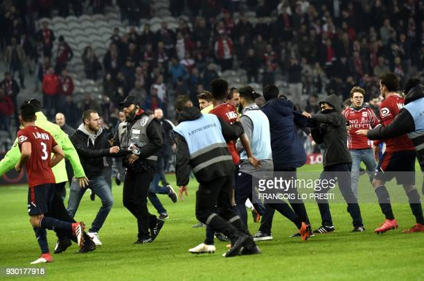 Lille' supporters invade the pitch at the end of the French L1 football match between Lille and Montpellier on March 10, 2018 at the Pierre Mauroy...