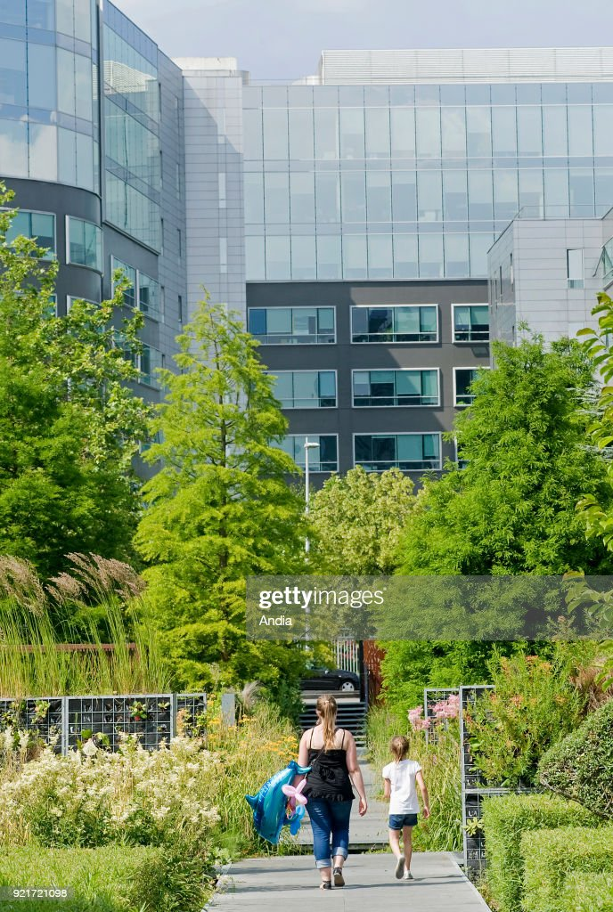 the Garden of the Giants ('jardin des geants') in the business district. Garden, greenery and office building facade.
