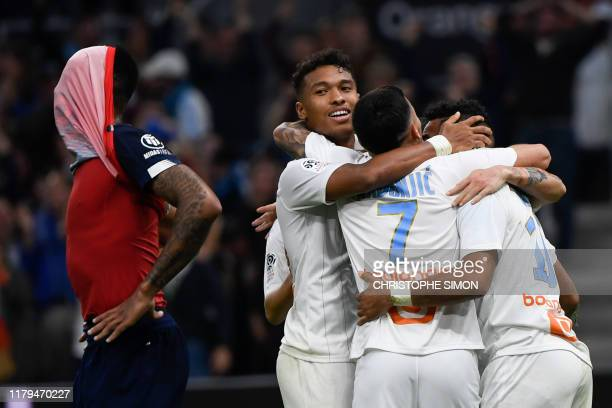 TOPSHOT Lille's Brazilian defender Gabriel dos Santos Magalhaes who scores an own goal reacts as Marseille's players celebrate during the French L1...