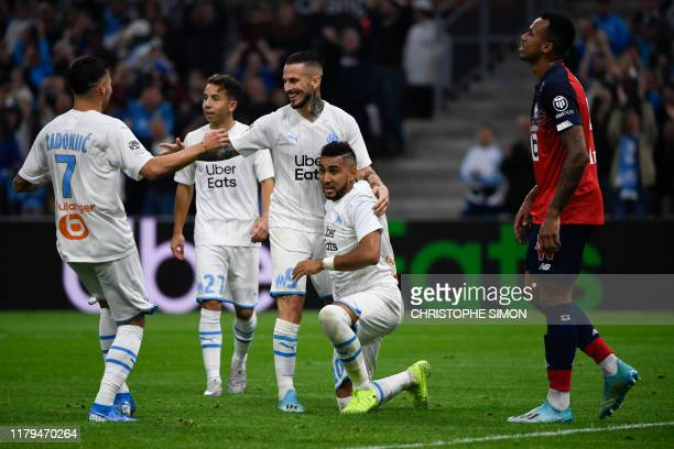 Lille's Brazilian defender Gabriel dos Santos Magalhaes who scores an own goal reacts as Marseille's players celebrate during the French L1 football...