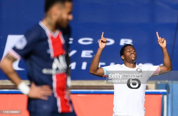Lille's Canadian forward Jonathan David celebrates after scoring a goal as Paris Saint-Germain's Brazilian forward Neymar reacts during the French L1...
