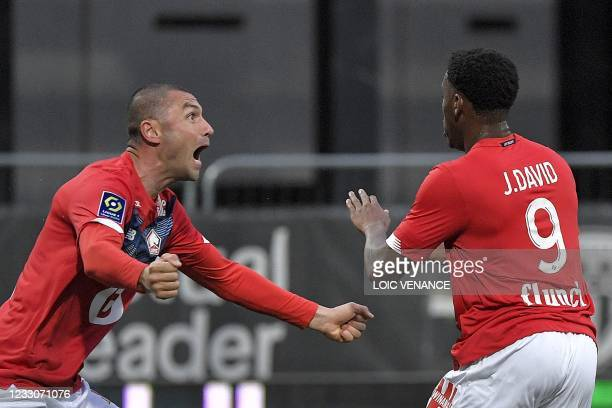 Lille's Canadian forward Jonathan David is congratulated by Lille's Turkish forward Burak Yilmaz after scoring a goal during the French L1 football...