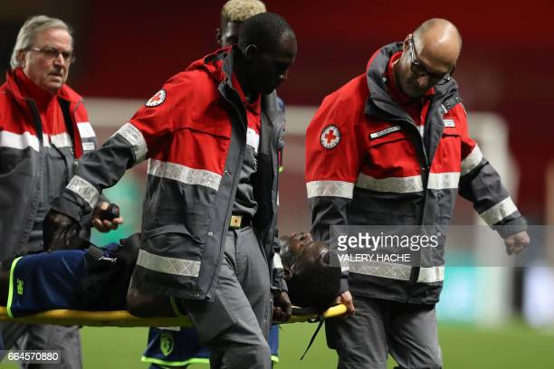 Lille's French defender Adama Soumaoro is evacuated on a stretcher after an injury during the French Cup quarter final football match between Monaco...
