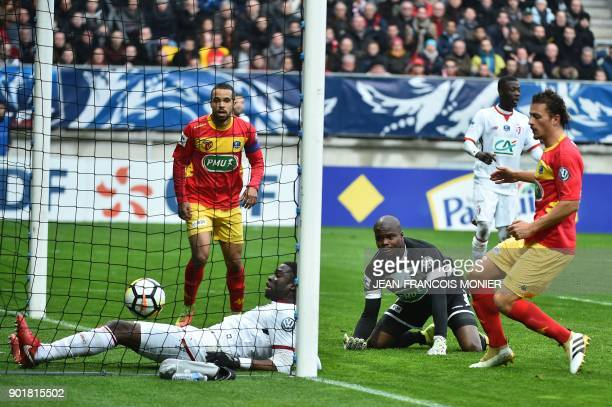 Lille's French defender Adama Soumaoro scores next to Le Mans' French goalkeeper Cedric Mensah during the French Cup football match between Le Mans...