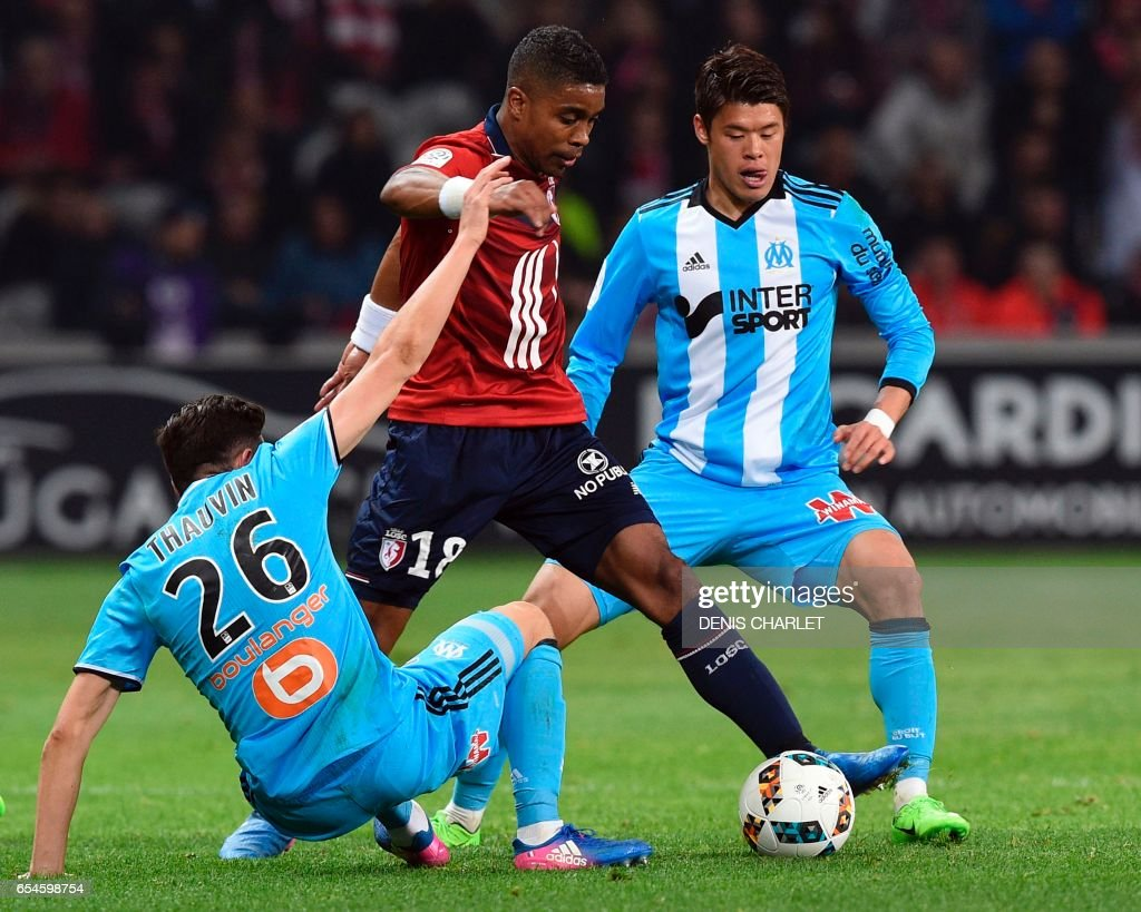 Lille's French defender Franck Beria (C) vies with Olympique de Marseille's French midfielder Florian Thauvin (L) and Olympique de Marseille's Japanese defender Hiroki Sakai during the French L1 football match between Lille OSC (LOSC) and Marseille on March 17, 2017 at the Pierre-Mauroy Stadium in Villeneuve d'Ascq, near Lille, northern France. /