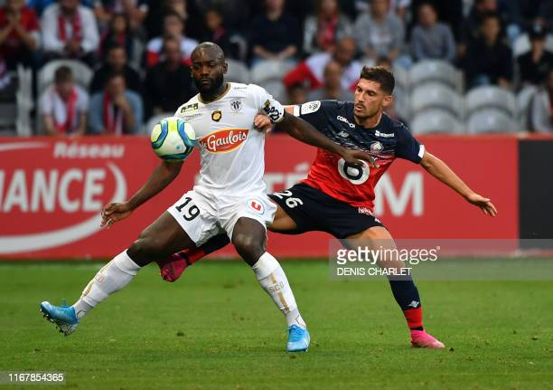 Lille's French forward Jeremy Pied vies for the ball with Angers' Cameroon forward Stephane Bahoken during the French L1 football match between Lille...