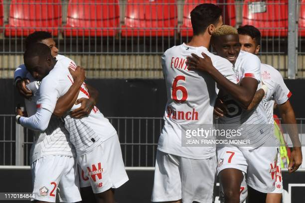 Lille's French forward Jonathan Ikone is congratulated by Lille's Mozambican forward Reinildo Mandava after scoring a goal during the French L1...