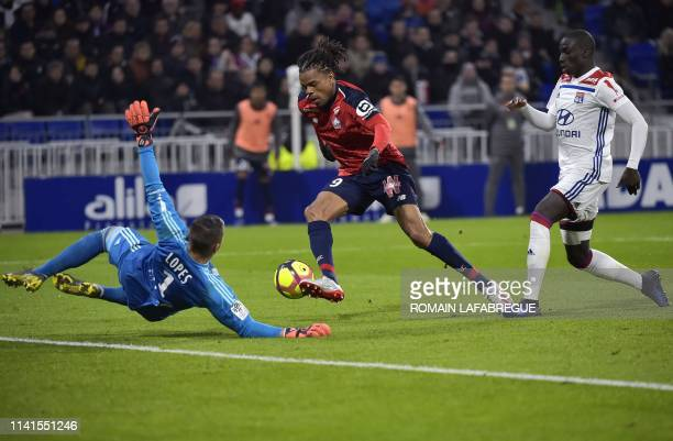 Lille's French forward Loic Remy vies with Lyon's Portuguese goalkeeper Anthony Lopes and Lyon's French defender Ferland Mendy and scores a goal...