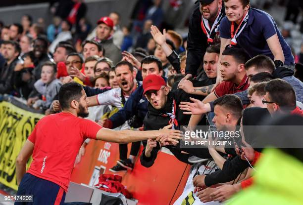 Lille's French forward Yassine Benzia is congratulated by supporters at the end of the French L1 football match between Lille and Metz on April 28...