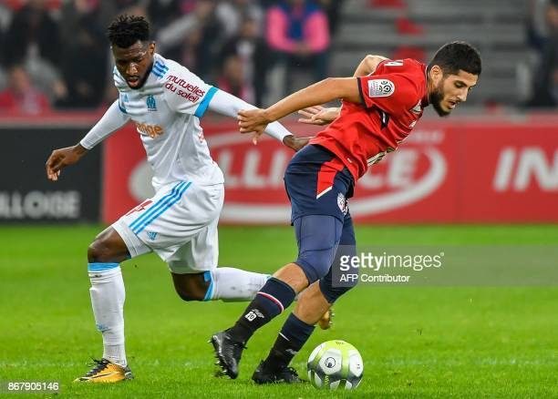 Lille's French forward Yassine Benzia vies with Marseille's Cameroonian midfielder Andre Zambo Anguissa during the French L1 football match between...