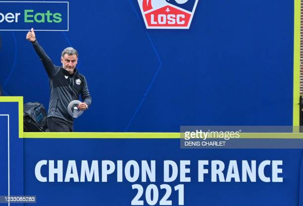Lille's French head coach Christophe Galtier raises his thumb as Lille's players celebrate with France's L1 football championship trophy at the cub's...