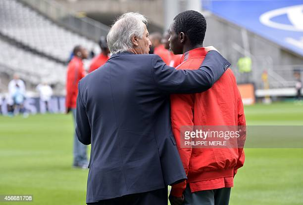 Lille's French head coach Rene Girard speaks with Lille's Spanish midfielder Adama Traore before the French L1 football match Lyon vs Lille on...