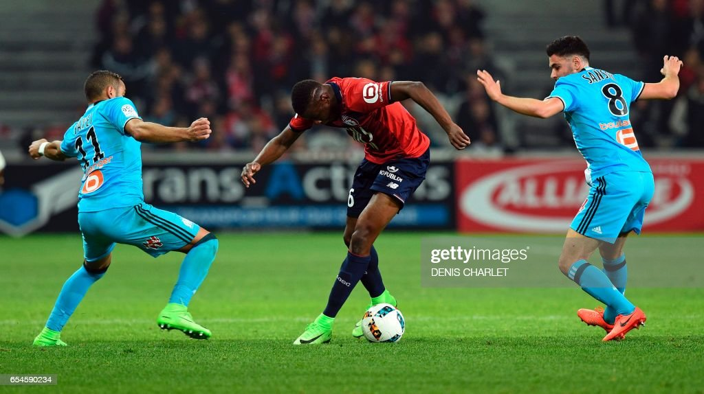 Lille's French midfielder Ibrahim Amadou (C) vies with Morgan Samson (R) and Olympique de Marseille's French forward Dimitri Payet during the French L1 football match between Lille OSC (LOSC) and Marseille on March 17, 2017 at the Pierre-Mauroy Stadium in Villeneuve d'Ascq, near Lille, northern France. /