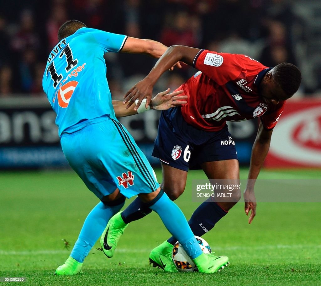 Lille's French midfielder Ibrahim Amadou (R) vies with Olympique de Marseille's French forward Dimitri Payet during the French L1 football match between Lille OSC (LOSC) and Marseille on March 17, 2017 at the Pierre-Mauroy Stadium in Villeneuve d'Ascq, near Lille, northern France. /