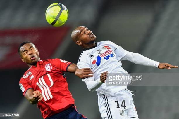 Lille's Ivorian defender KouadioYves Dabila and Amiens' Congolese midfielder Gael Kakuta go for a header during the French L1 football match played...
