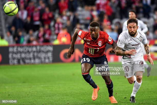 Lille's Ivorian forward Nicolas Pepe and Metz's Luxemburg defender Vahid Selimovic eye the ball during the French L1 football match between Lille and...
