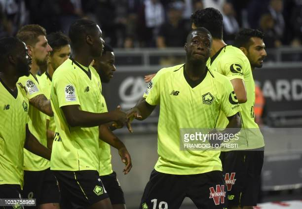 Lille's Ivorian forward Nicolas Pepe celebrates with teammates after scoring a goal during the French L1 football match between Amiens and Lille at...