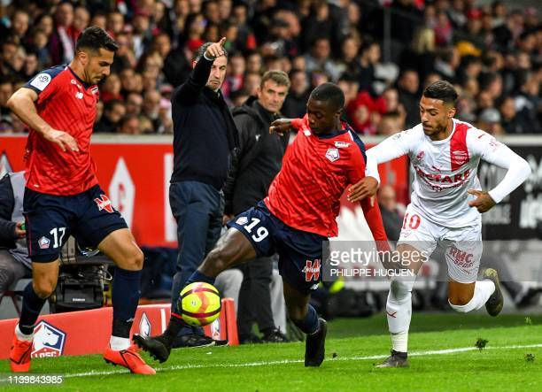 Lille's Ivorian forward Nicolas Pepe fights for the ball with Nîmes' Gabonese midfielder Denis Bouanga during the French L1 football match between...