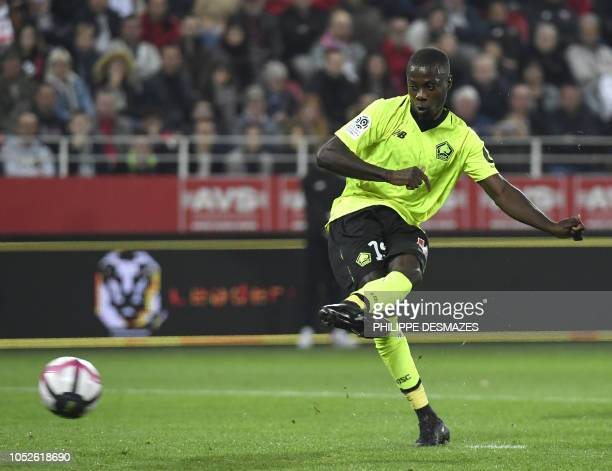 Lille's Ivorian forward Nicolas Pepe shoots and scores a penalty during the French L1 football match between Dijon Football Côted'Or and LOSC Lille...