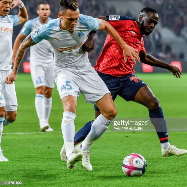 Lille's midfielder Jonathan Ikone vies with Marseille's Argentinian forward Lucas Ocampos during the French L1 football match between Lille and...
