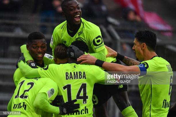 Lille's players celebrate after scoring a goal during the French L1 football match between Nimes and Lille on December 16 2018 at the Costieres...