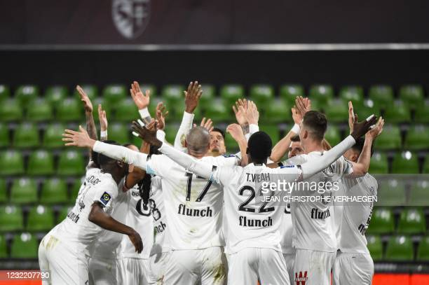 Lille's players celebrate after scoring a goal during the French L1 football match between Metz and Lille at Saint Symphorien stadium in...