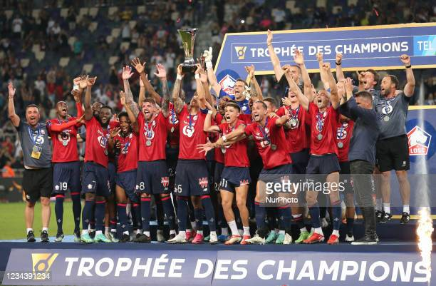 Lille's players celebrate with the trophy after winning the French Champions' Trophy final football match between Paris Saint-Germain and Lille at...