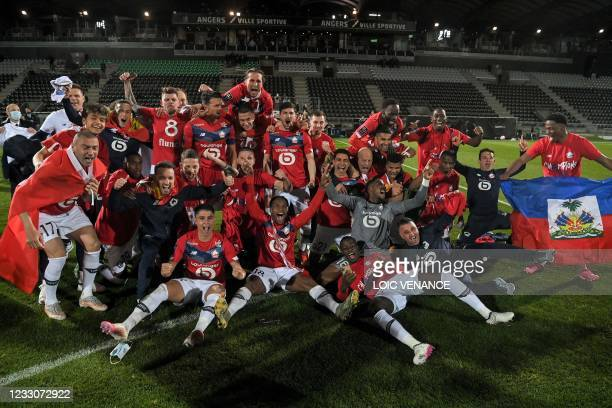 Lille's players pose for a group picture after winning the French L1 football match between Angers SCO and Lille OSC at The Raymond-Kopa Stadium in...