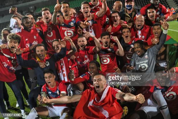 Lille's Turkish forward Burak Yilmaz and Lille's players pose for a group picture after winning the French L1 football match between Angers SCO and...