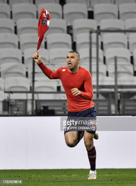 Lille's Turkish forward Burak Yilmaz celebrates after scoring during the French Ligue 1 football match between Olympique Lyonnais and LOSC Lille at...