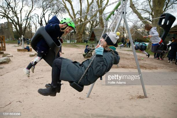 Lilli Geissendorfer and her daughter Della on a swing at Victoria Park playground on March 6, 2021 in London, England. Londoners are enjoying bright...