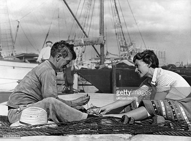 Lilli Palmer * Actress Germany with a fisher during the shooting of the film Between Time and Eternity director Arthur Maria Rabenalt Germany 1956