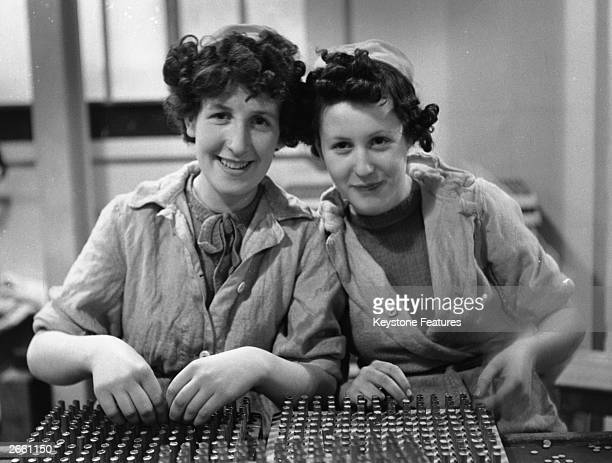 Lillian and Ivy Hulme packing a tray of bullets at an armaments factory in Staffordshire.