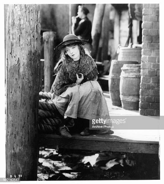 Lillian Gish sits on a dock in a scene from the film 'Broken Blossoms' 1919