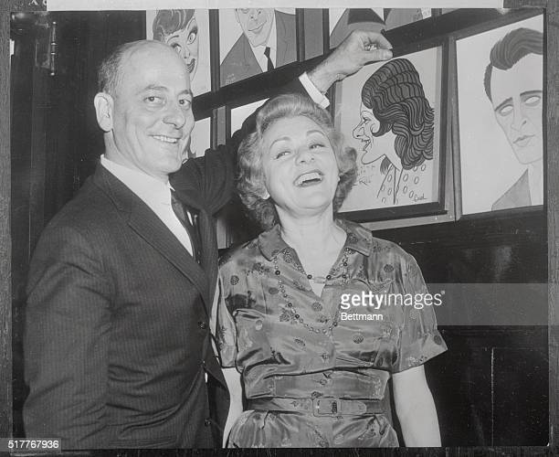 Lillian Roth one of the first celebrities to have her caricature hung on the walls of Sardi's back in the '30's happily watches host Vincent Sardi Jr...