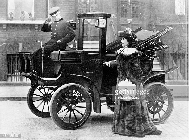 Lillie Langtry modelling a sable motoring coat Standing next to an electric City and Suburban car The driver tips his hat to the photographer