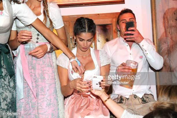 """Lilly Becker, touches Shermine Shahrivar, Julian Maurer during the """"Wiesnbummel by CathyHummels"""" as part of the Oktoberfest 2019 at Kaeferschaenke..."""