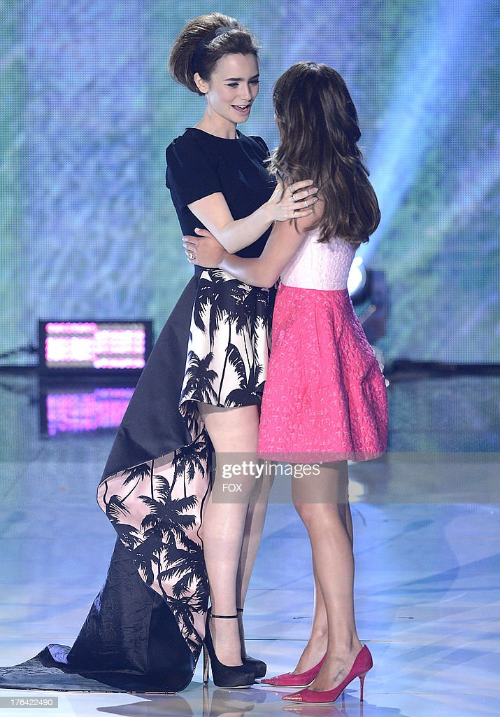 Lilly Collins (L) and Lea Michele speak onstage at the 2013 Teen Choice Awards at Gibson Amphitheater on August 11, 2013 in Universal City, California.