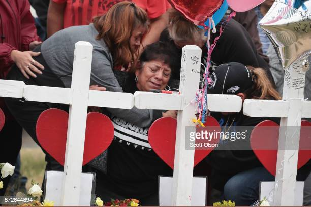 Lilly Navejan is comforted after breaking down while visiting a memorial where 26 crosses were placed to honor the 26 victims killed at the First...