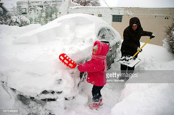 Lilly Shweikhard and Tara Shweikhard dig out after a five mile wide band of lake-effect snow dumped more than two feet of snow and closed a 16-mile...