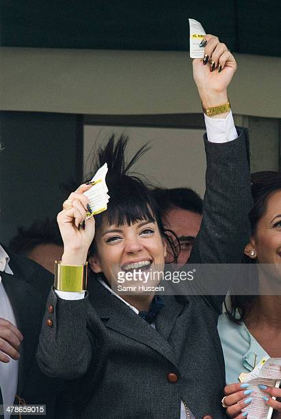 Lily Allen celebrates winning a bet in the Gold Cup during The Cheltenham Festival at Cheltenham Racecourse on March 14 2014 in Cheltenham England