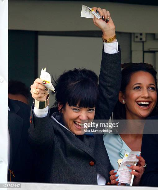 Lily Allen cheers and celebrates as she watches the Cheltenham Gold Cup on Day 4 of the Cheltenham Festival at Cheltenham Racecourse on March 14 2014...