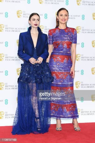 Lily Collins and Olga Kurylenko pose in the press room during the EE British Academy Film Awards at Royal Albert Hall on February 10 2019 in London...