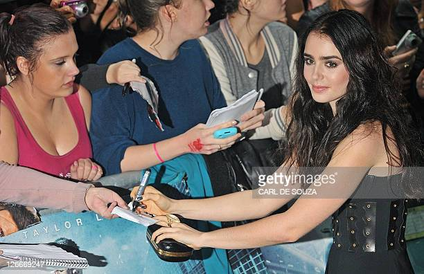 Lily Collins daughter of British pop musician Phil Collins signs autographs for fans as she arrives for the European Premiere of the film 'Abduction'...
