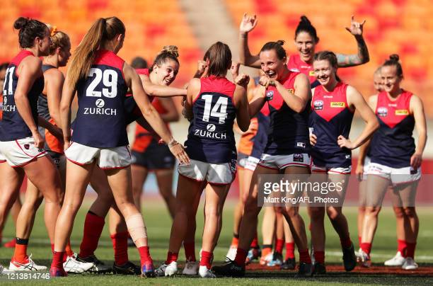 Lily Mithen of the Demons celebrates victory with team mates after the AFLW Semi Final match between the Greater Western Sydney Giants and the...