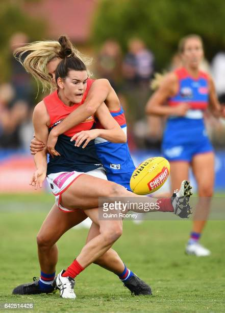 Lily Mithen of the Demons kicks whilst being tackled by Bailey Hunt of the Bulldogs during the Women's round three match between the Western Bulldogs...