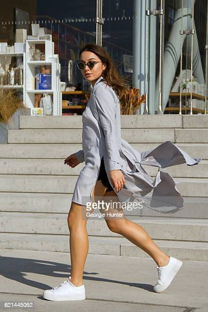 Lily Montasser wearing white DKNY leather sneakers grey silk long tunic top with slit by Vince Miss Pap grey cotton trench coat with waist tie and...